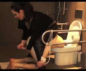 Slaaf met zijn hoofd in de wc en haar lul in zijn kont
