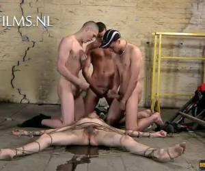 Drie mannen spuiten over vastgebonden slaafje heen